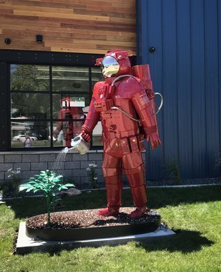 Hunter Brown; Pioneer, 2020, Original Sculpture Steel, 48 x 120 inches. Artwork description: 241 Pioneer is a large stainless steel sculpture constructed from stainless steel with a red powder- coat finish. This 10  astronaut is mounted to a reservoir base which circulates water through his body to watering can, that waters a metal marijuana plant. The reservoir is covered with expanded ...