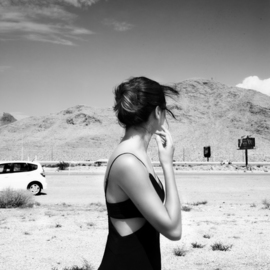 Aliona Kuznetsova: 'lost in the wind', 2020 Black and White Photograph, Romance. Artist Description: A woman facing away from the camera, yet we can understand she is overwhelmed. A gust of wind moved her hair and we can also see a fragment of a car behind her. ...