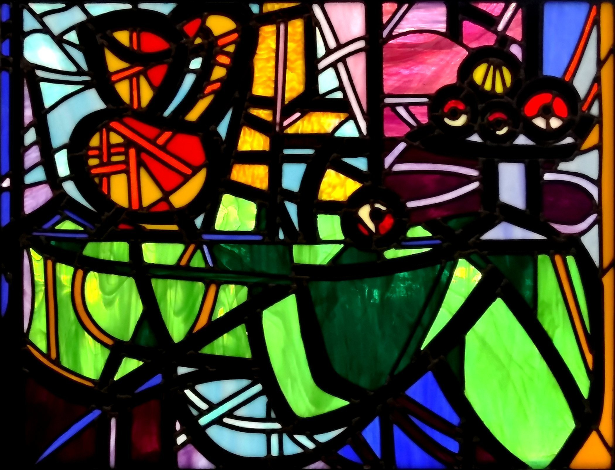 Iva Kalikow: 'Still Life Pitcher Fruit Bowl', 2020 Stained Glass, Still Life. This leaded stained glass art panel is inspired by Picasso and consists of 300 hand- cut pieces of 16 different colors and textures of glass.  I chose very bold colors of glass to emphasize the cubist drama.  It is framed in a 2 inch wide oak frame stained black and ...