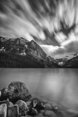Jon Glaser: 'Falling Sky', 2013 Black and White Photograph, Landscape. Artist Description: This Photograph was taken in Lake Louis, which is located in Banff National Park. The lake was calm while the clouds moved swiftly across the sky. This image was created using a longer exposure in the camera. The mountains have snow on them while the trees at the ...