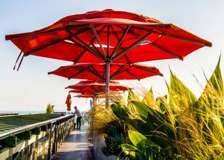 Dick Drechsler: 'the umbrellas of venice', 2018 Color Photograph, Urban. Artist Description: Towering over the Pacific Ocean this restaurant shelters its patrons from the sun with these colorful red umbrellas. ...