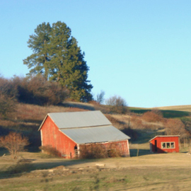 red barn casts evening shadow
