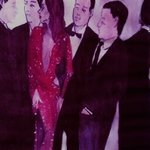 Woman in Sparkling Red Dress with Men  By Harry Weisburd